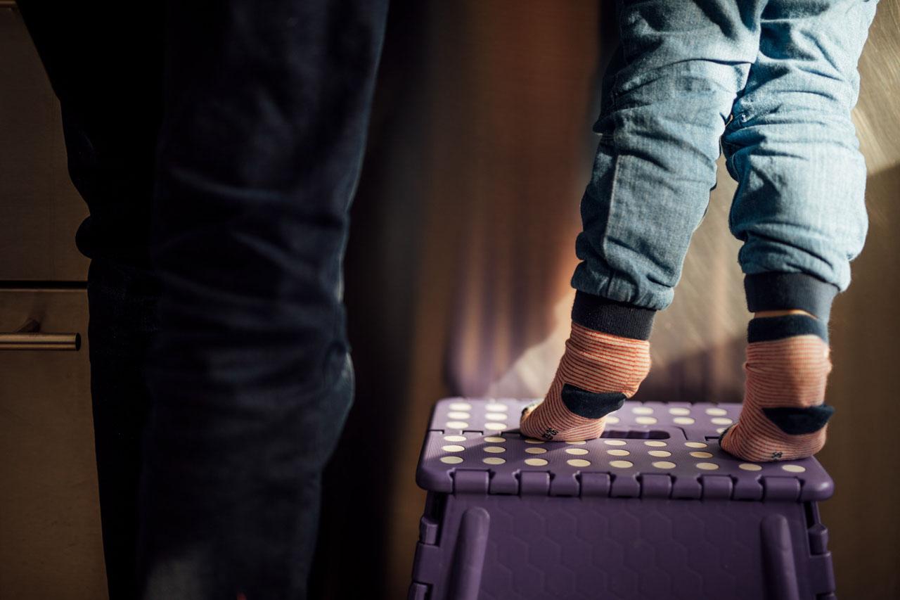 Die Beine eines Kindes auf einem Hocker stehend