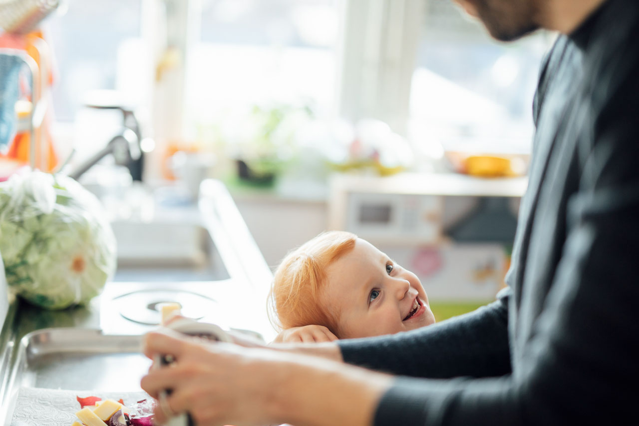 Kind schaut erwartungsvoll den Vater an , welcher in der Küche steht