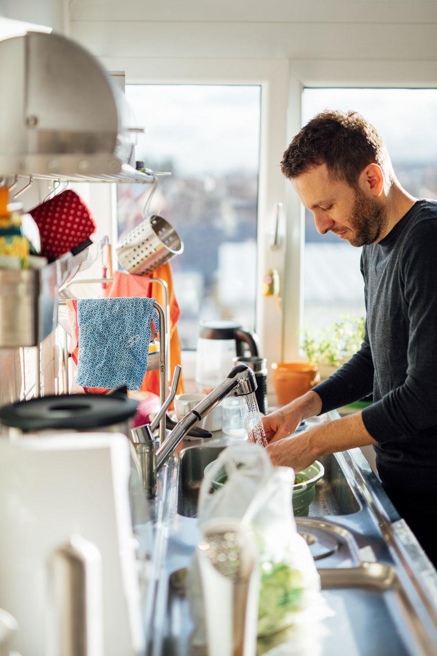 Vater steht in der Küche und macht den Abwasch
