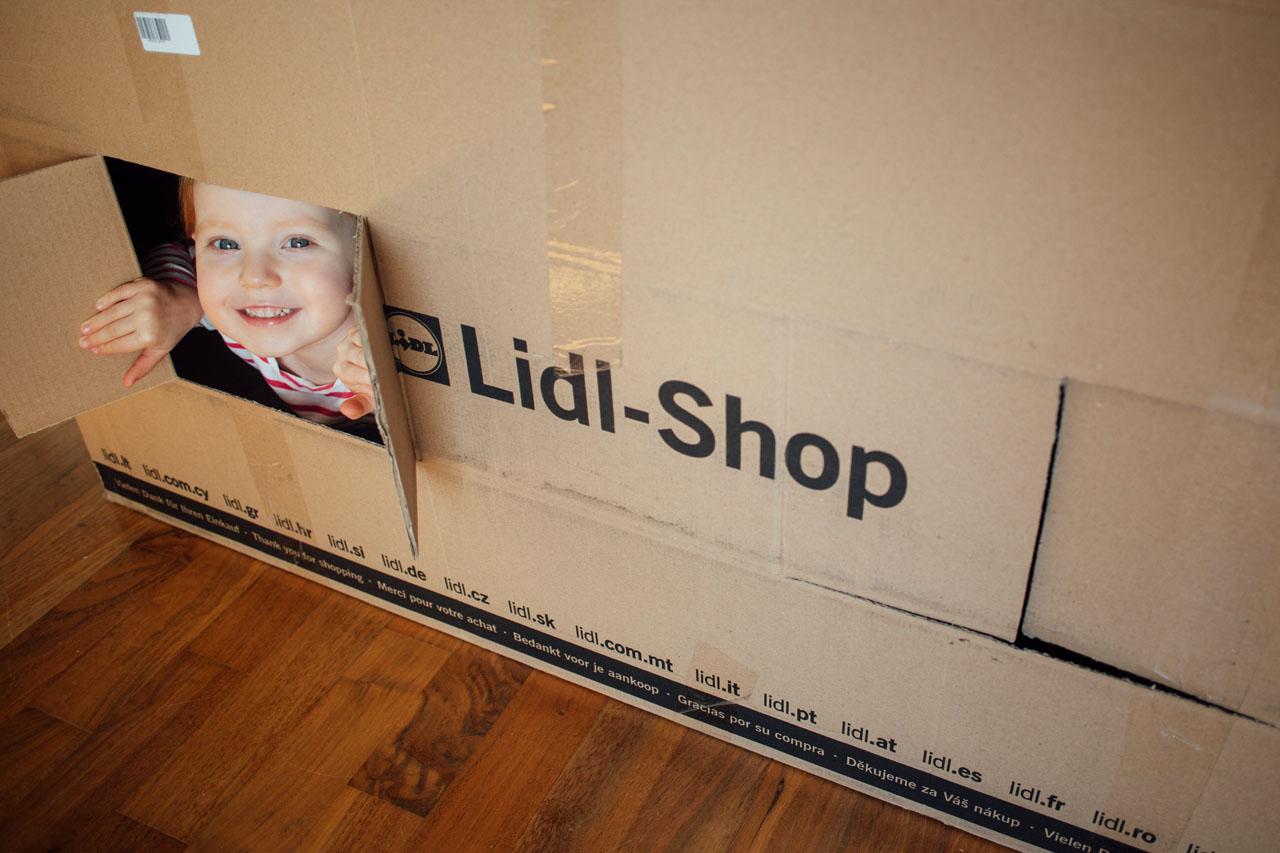 Kind schaut aus einem im Pappkarton eingeritzten Fenster