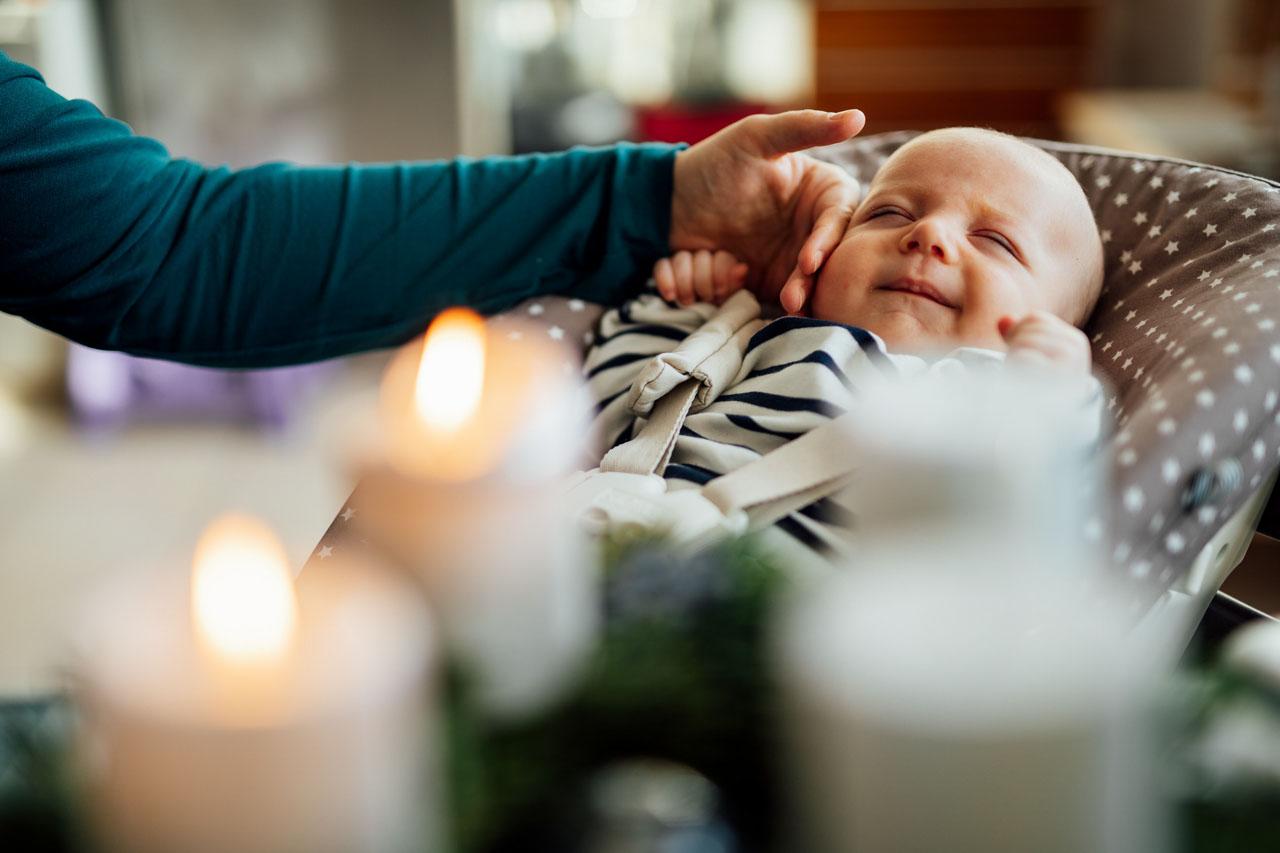 Schlafendes Baby liegt in der Wiege am Adventskranz