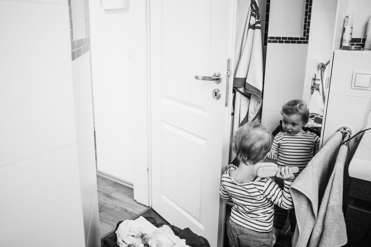 Zwei Geschwister kämmen sich im Badezimmer die Haare