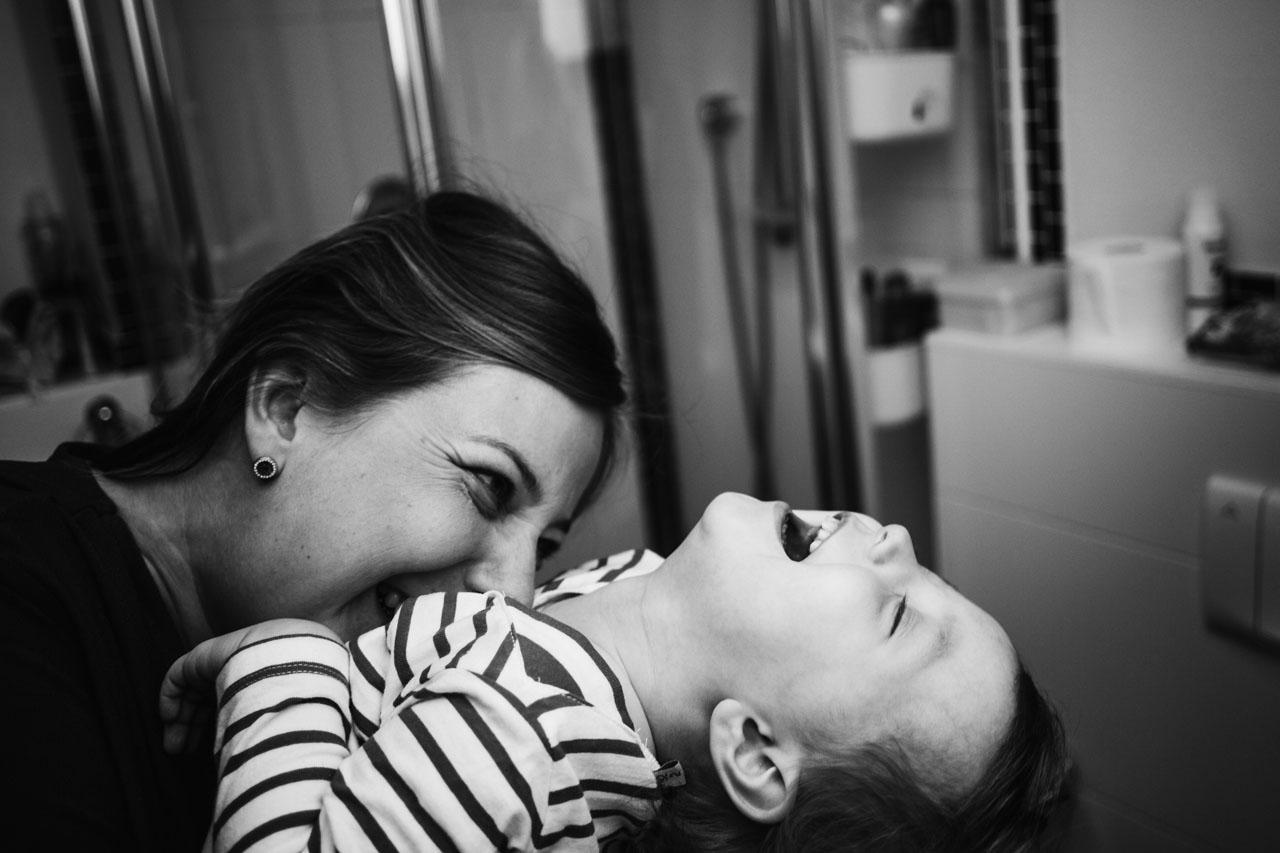 Mutter kitzelt ihr lachendes Kind
