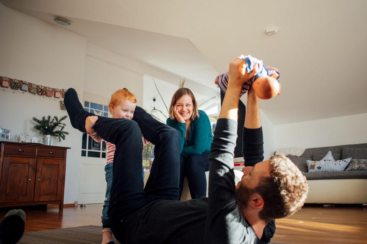 Familie spielt mit ihrem Kind lachend auf dem Teppich