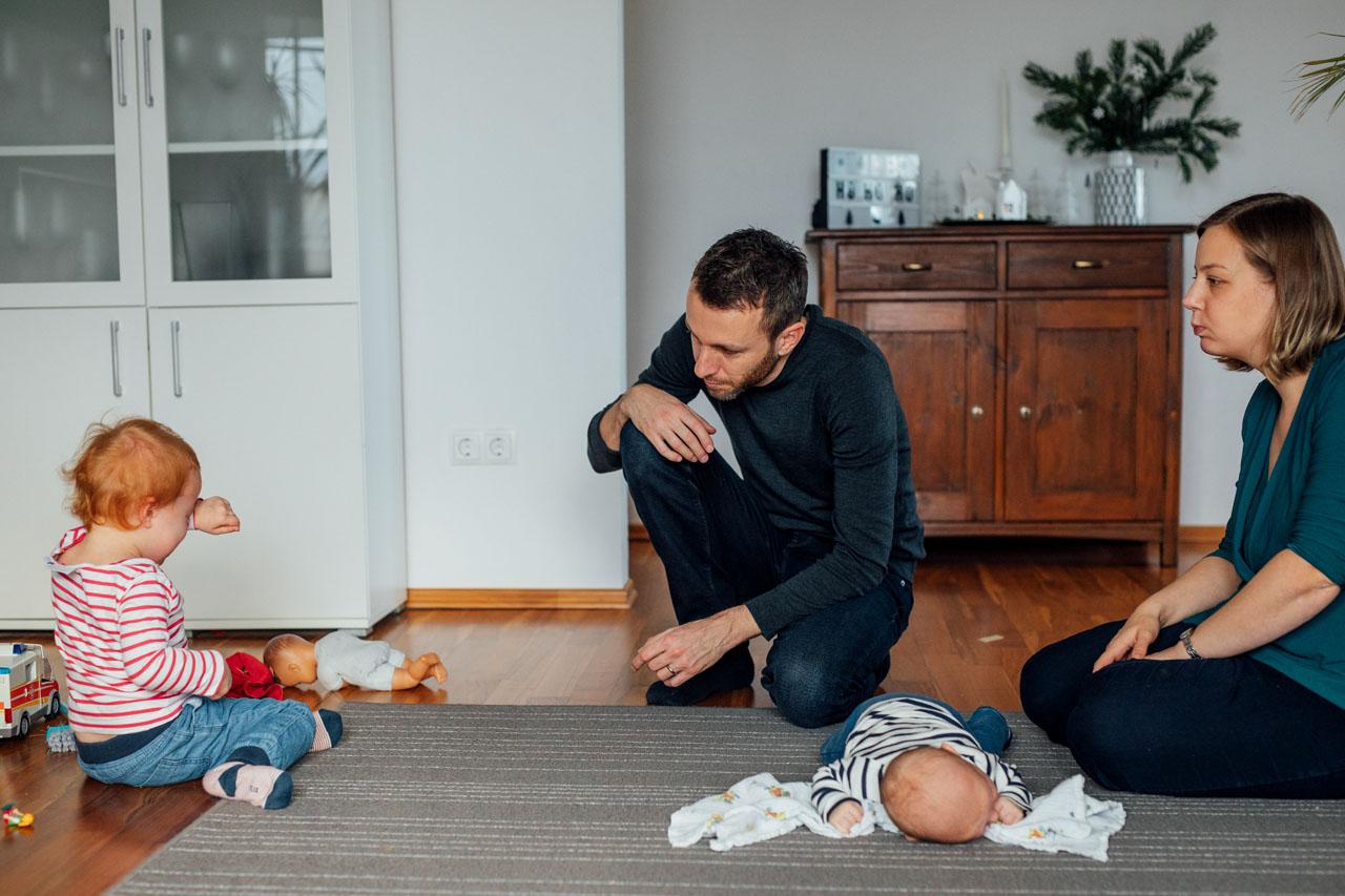 Eltern mit zwei Kindern sitzen auf einem Teppich
