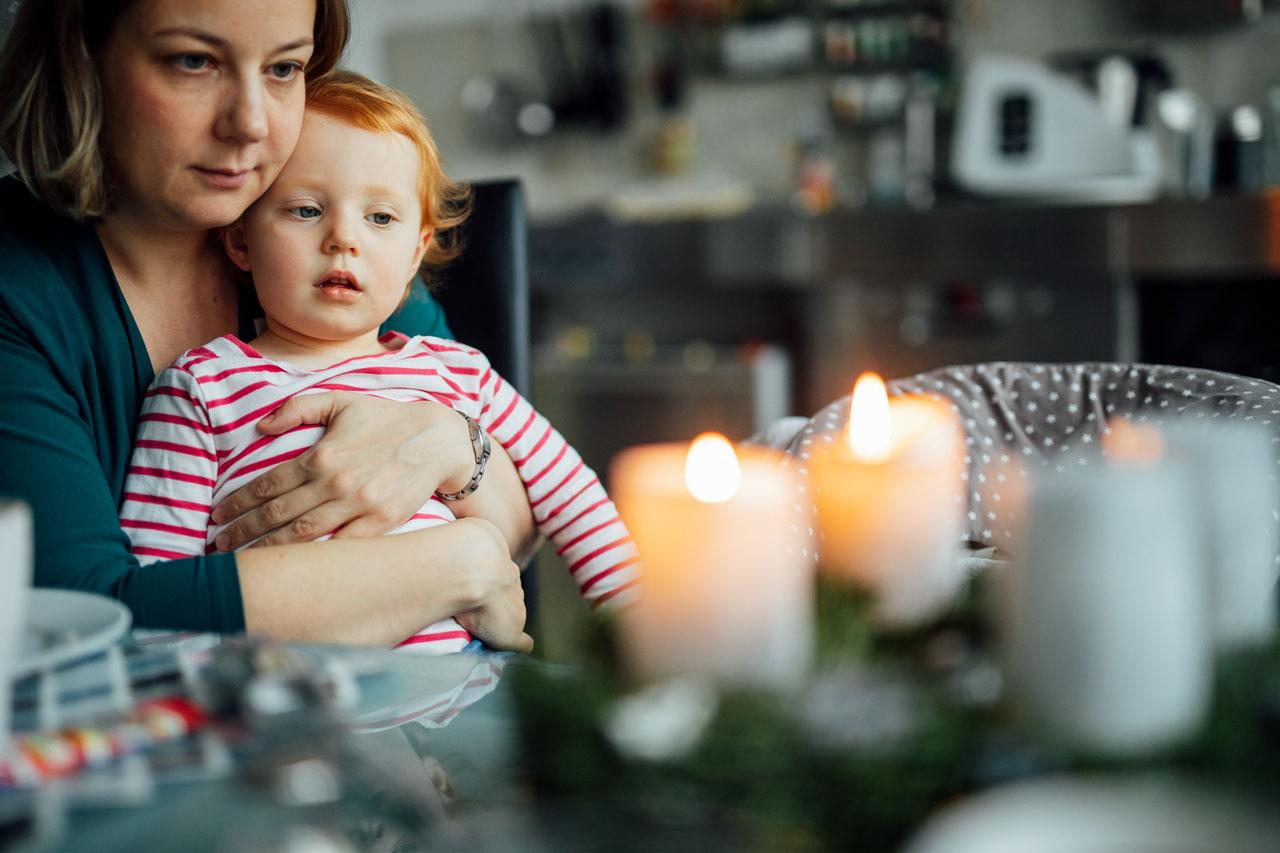 Mama und Tochter schauen auf Kerzen