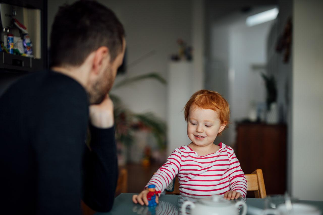 Kind spielt mit einer Figur am Tisch