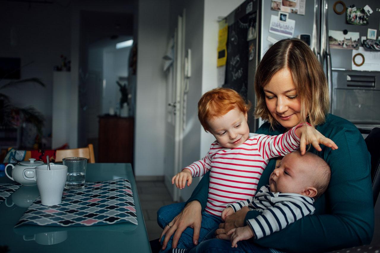 Mutter sitzt mit ihrem Kind und Baby am Küchentisch