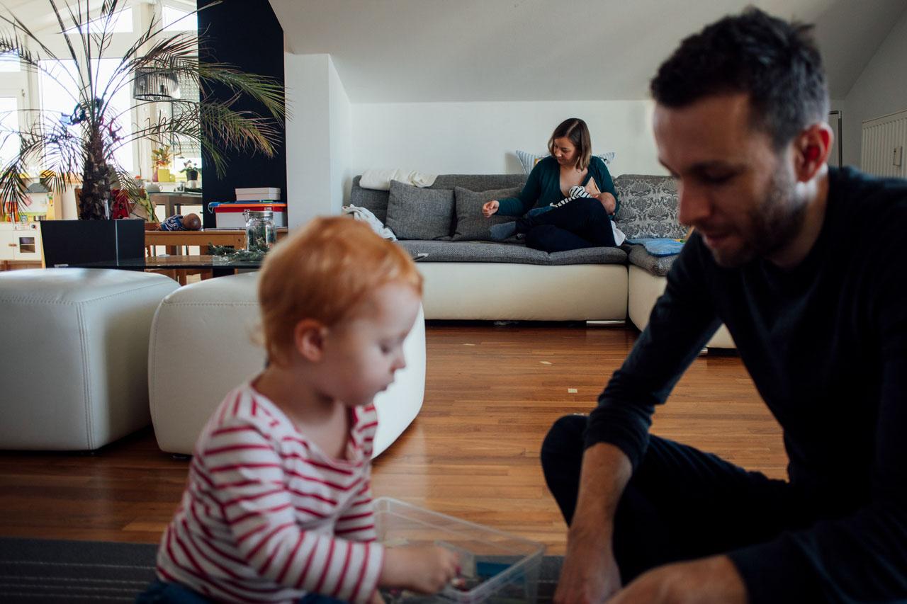 Vater spielt mit Kind während die Mutter das Baby stillt