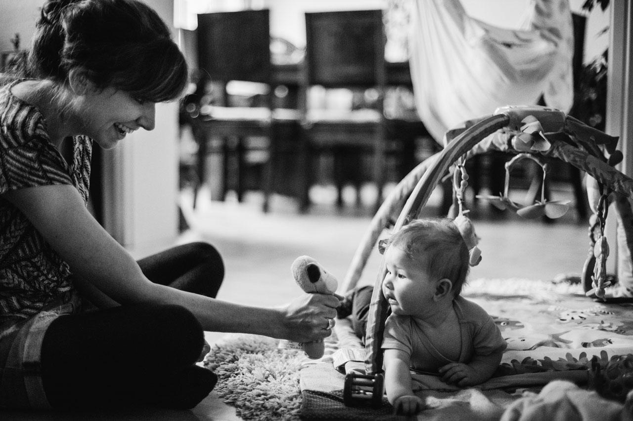 Baby liegt auf dem Bauch, Mutter zeigt ihr ein Kuscheltier