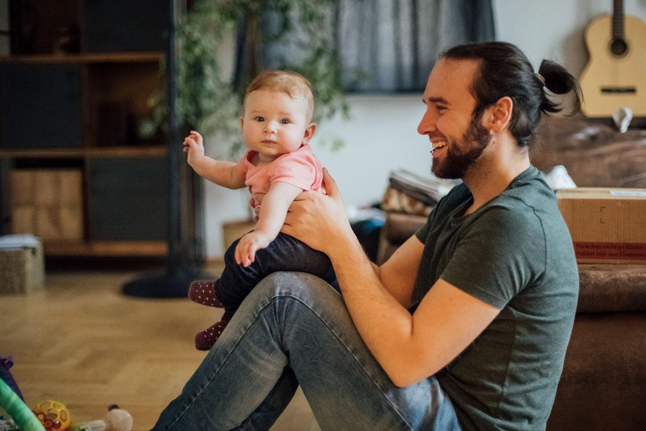 Vater hält das Baby und lacht, währenddessen das Baby in die Kamera schaut