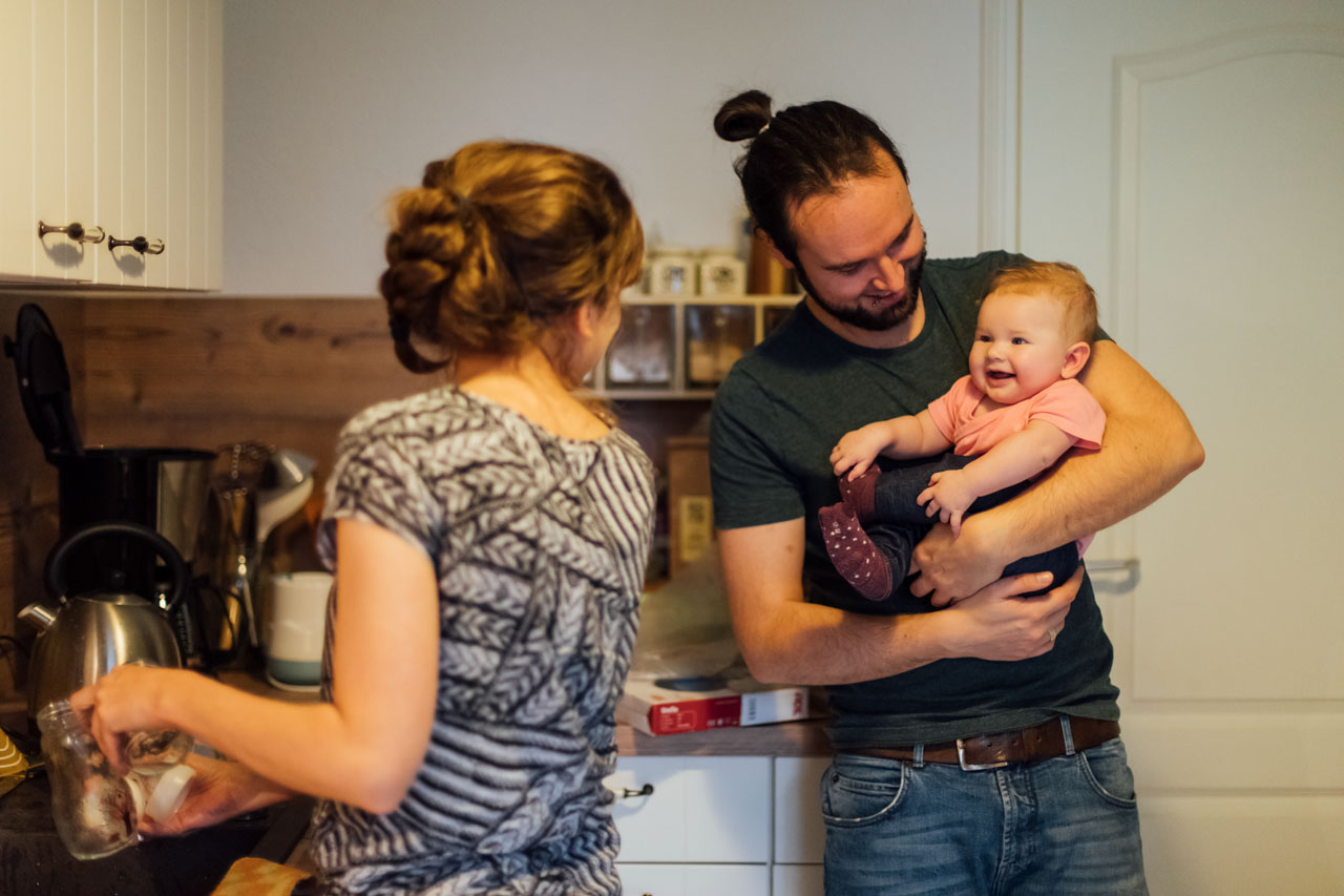 Vater hält das Baby auf dem Arm, dabei lächelt das Baby die Mutter an