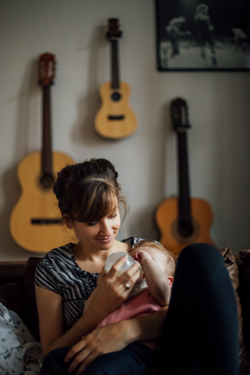 Mutter füttert das Baby mit Milch aus der Flasche, im Hintergrund an der Wand hängen drei Gitarren