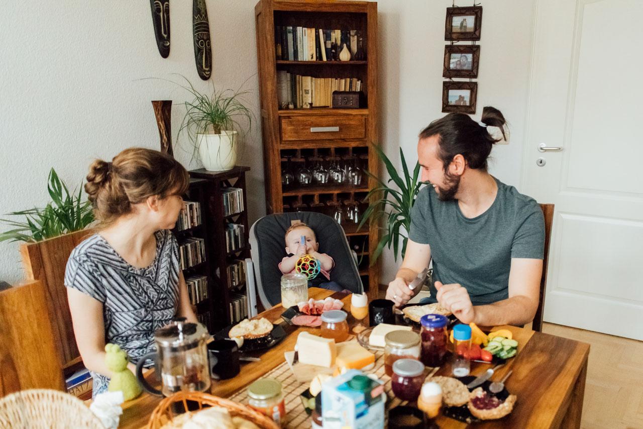 Eltern sitzen mit Kind am gedeckten Frühstückstisch