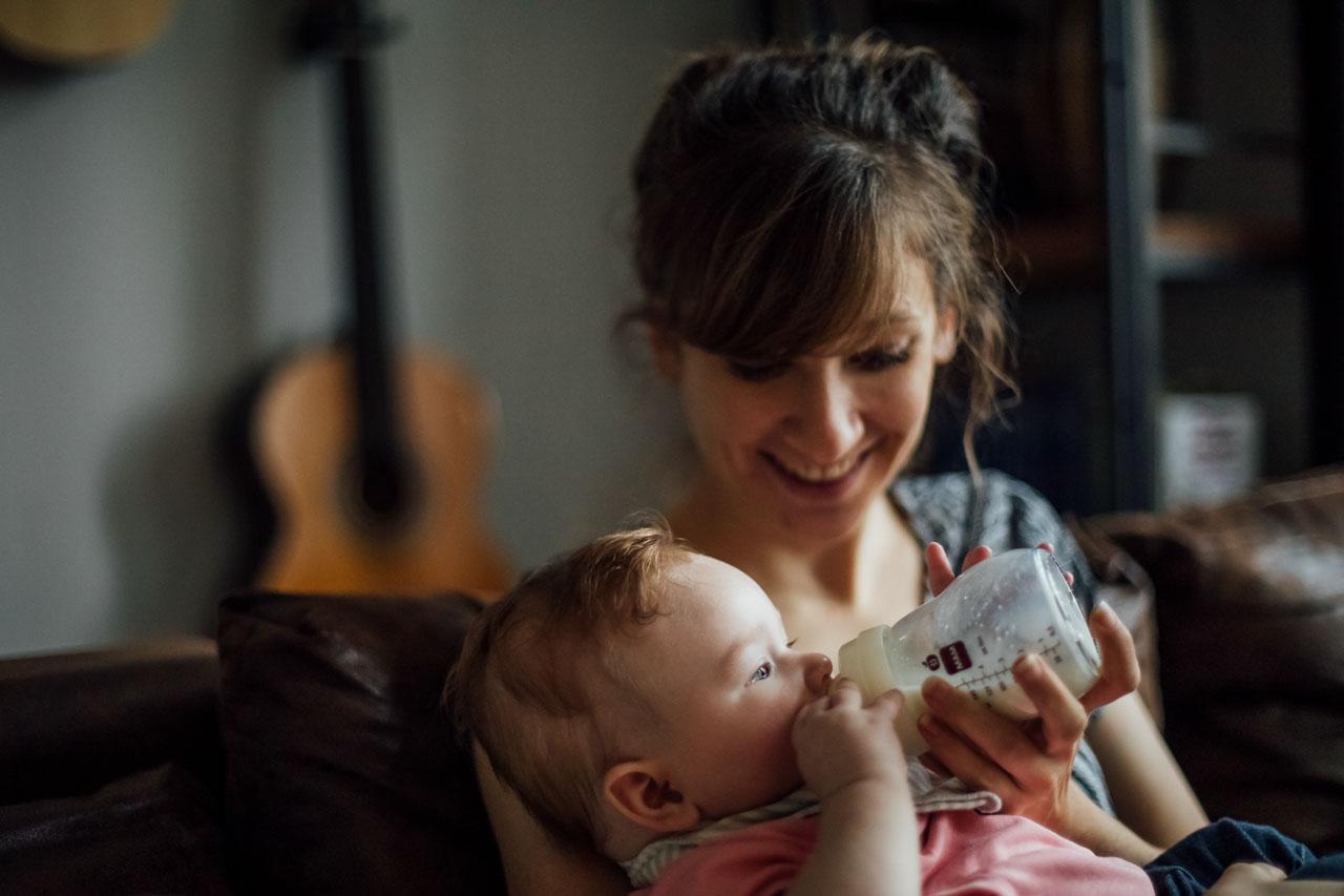 Mutter füttert das Baby mit Milch aus der Flasche