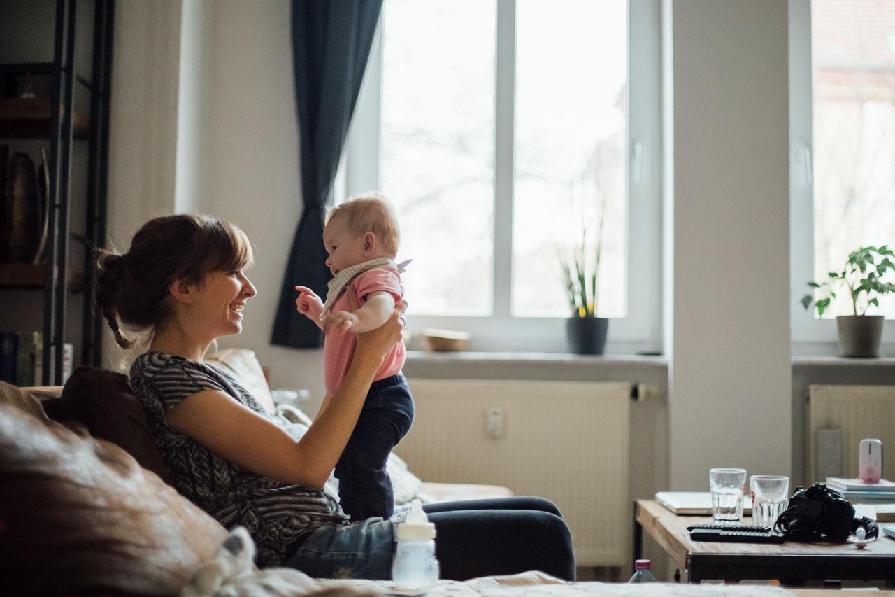 Mutter sitzt auf der Couch, hebt Baby hoch und sie lachen sich an