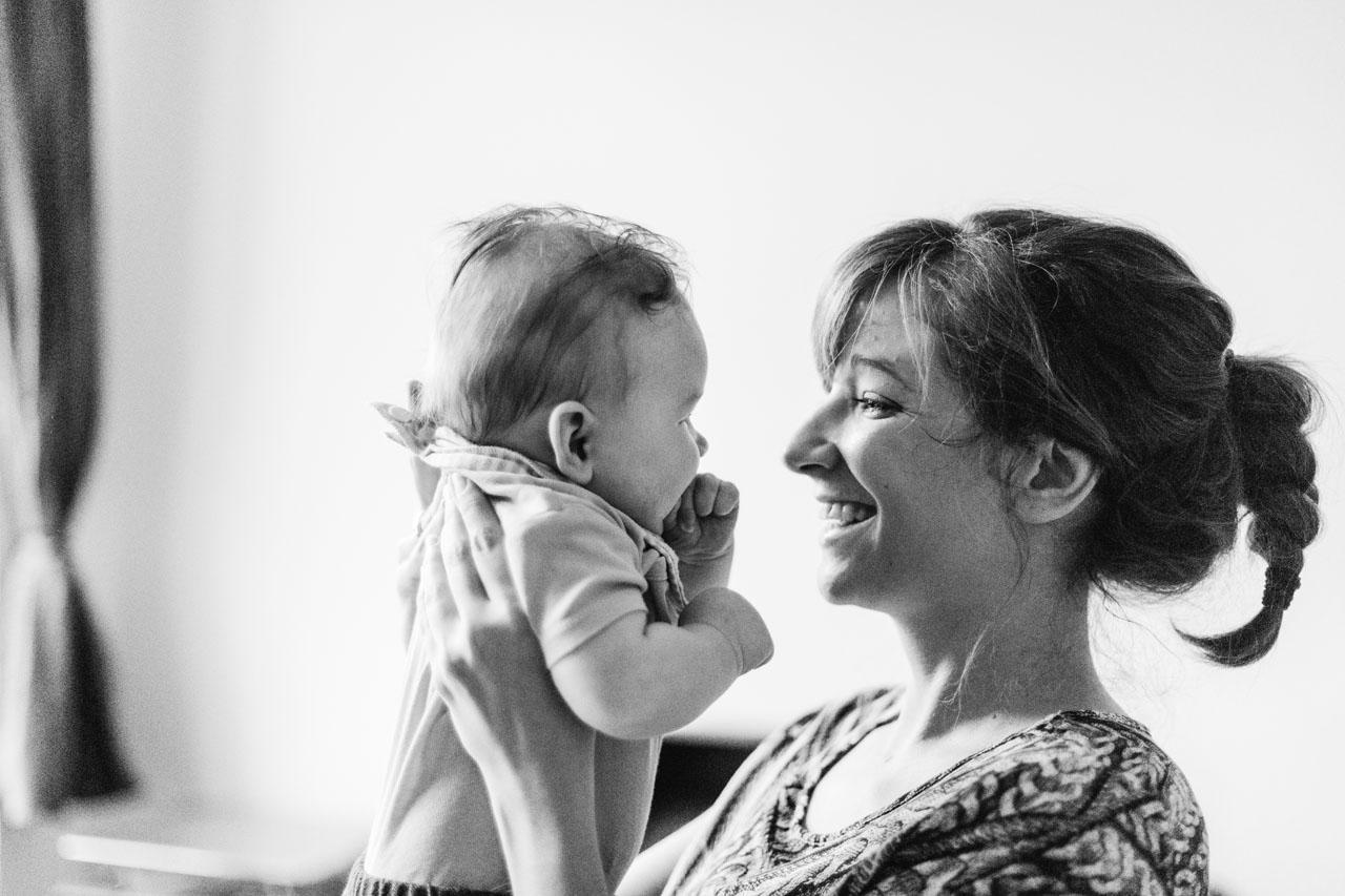 Mutter hält das Baby und sie lachen sich gegenseitig an