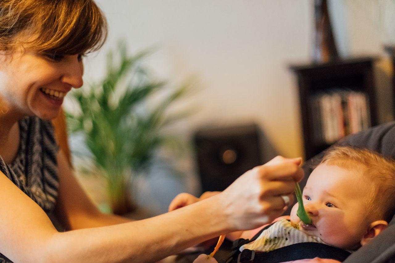 Mutter füttert das Kind mit einem Löffel