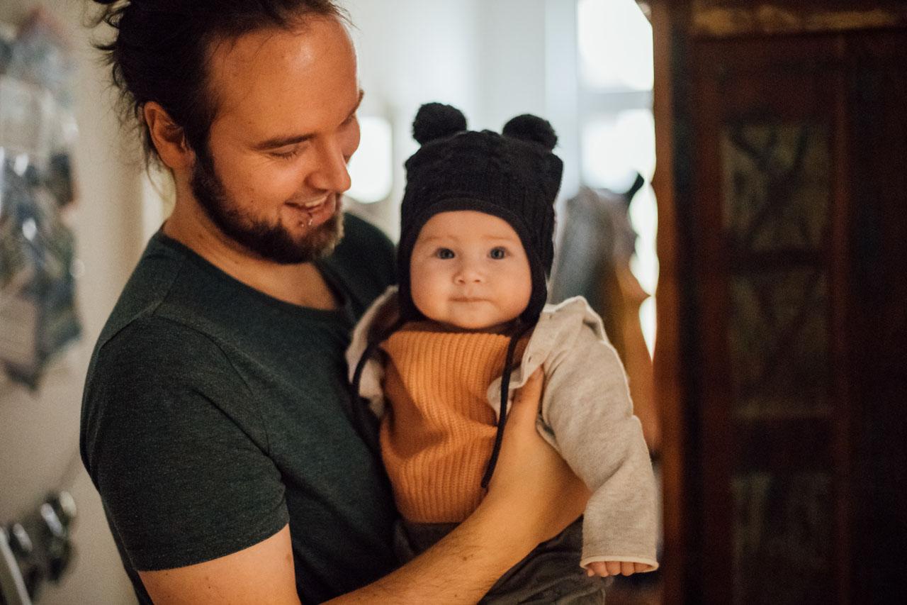 Vater lacht das Baby fröhlich an, Baby schaut in die Kamera