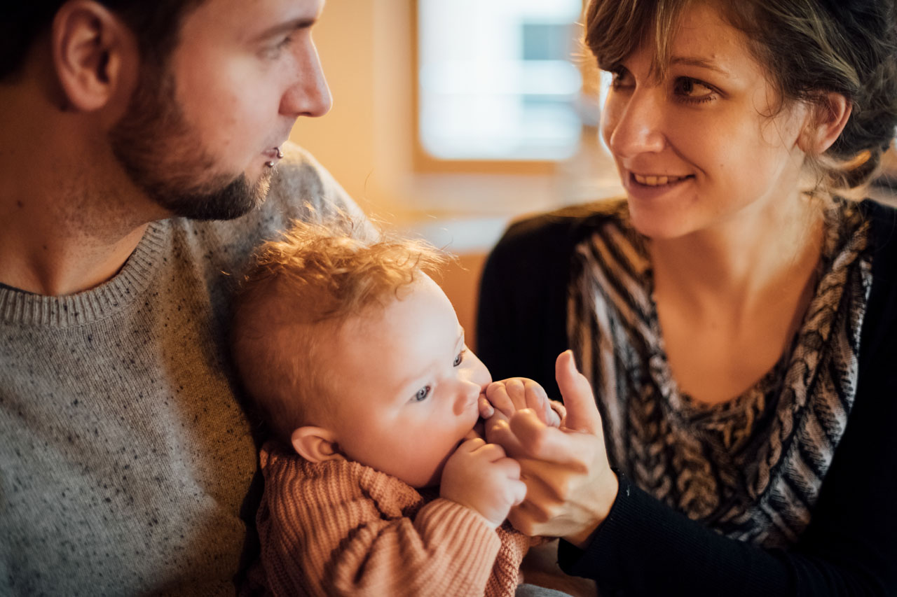 Eltern schauen sich an und Baby kaut auf den Händen der Mutter