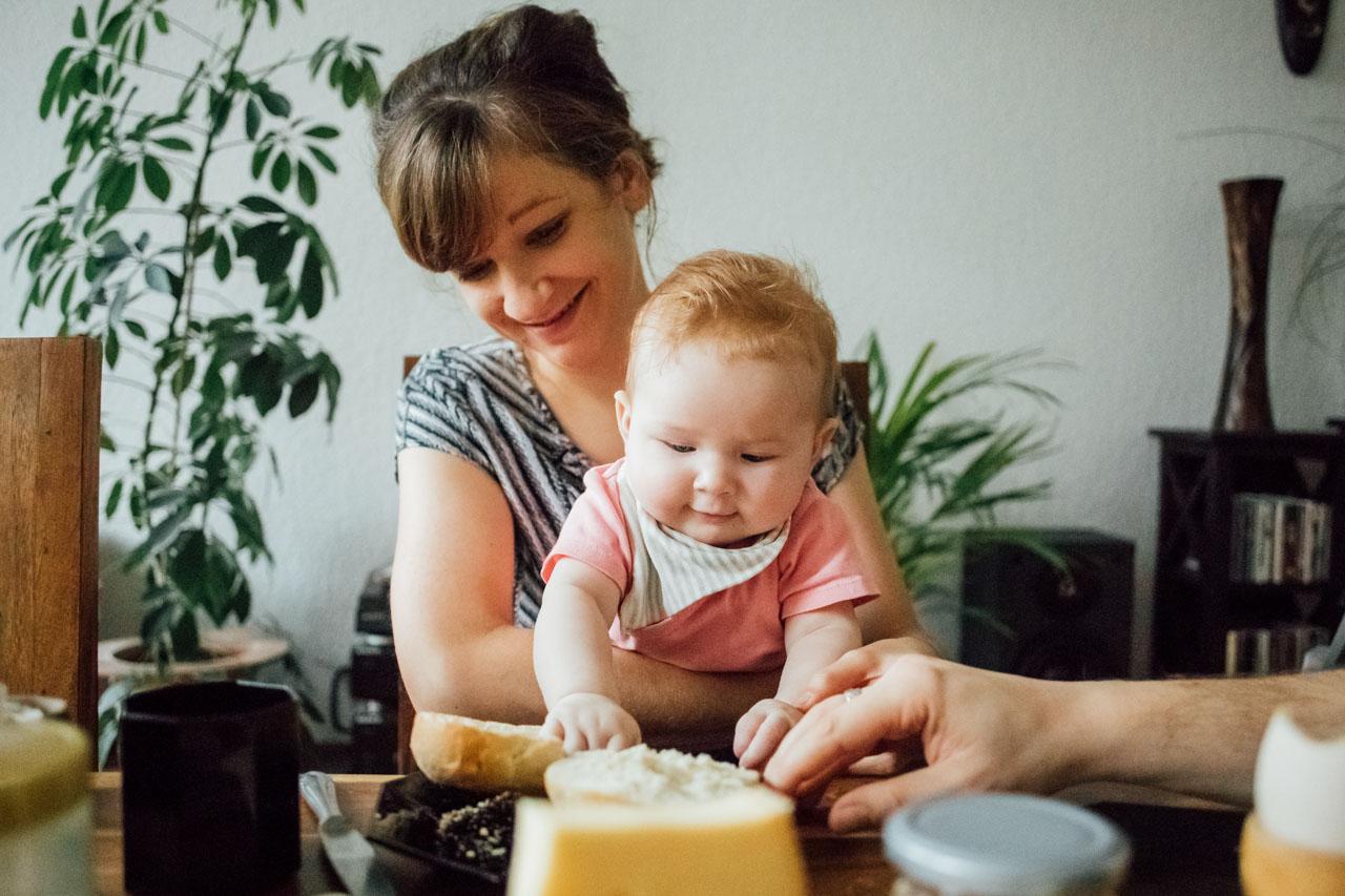 Mutter und Tochter sitzen am gedeckten Frühstückstisch