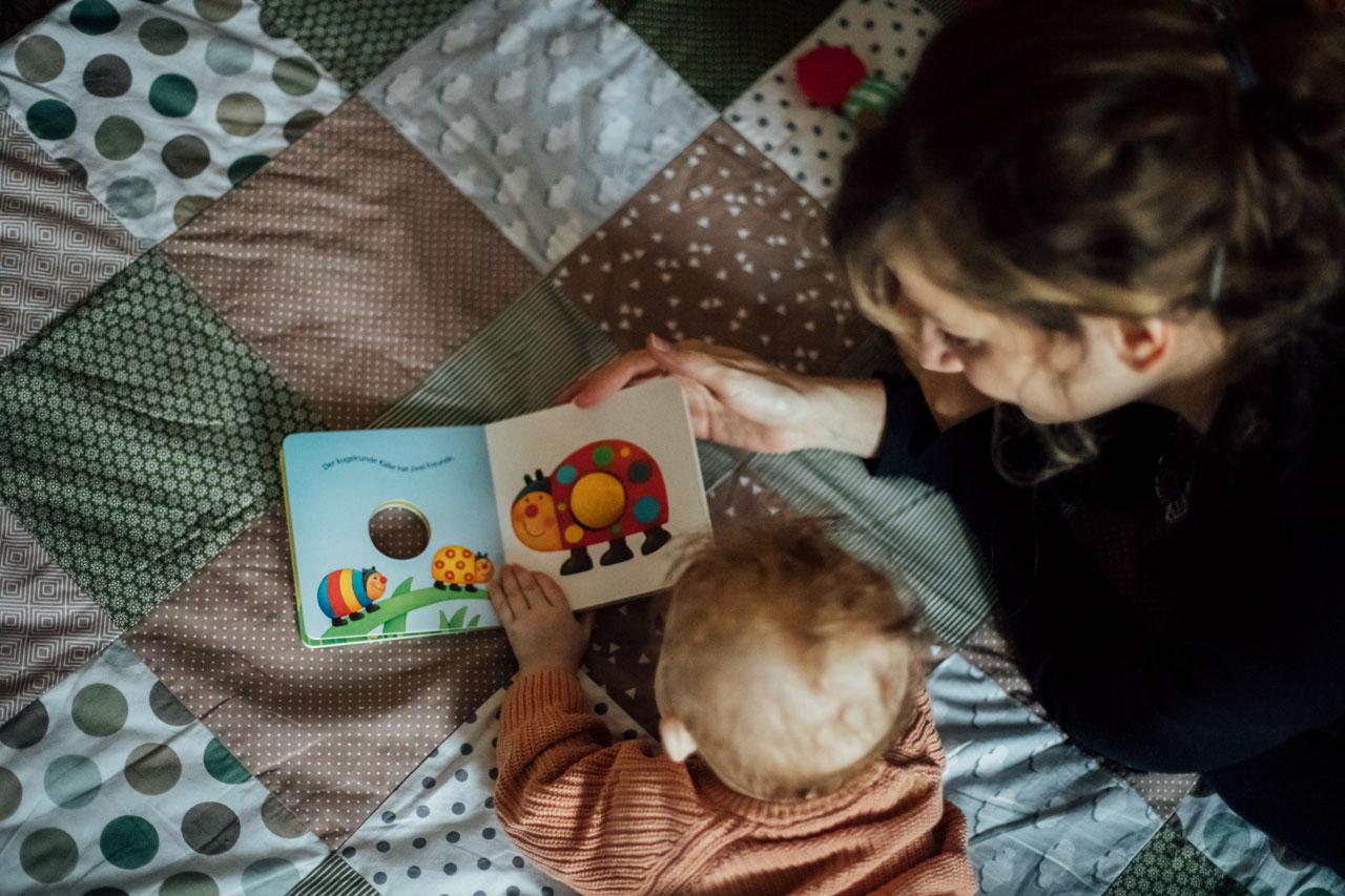 Mutter und Baby schauen sich ein Bilderbuch mit Käfern an