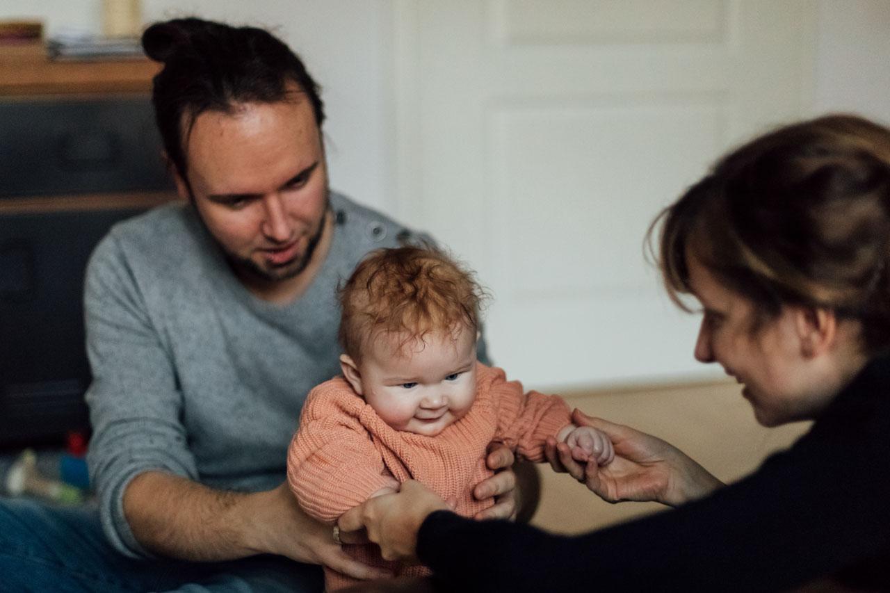 Baby sitzt auf den Schoß des Vaters und Mutter greift die Hände des Kindes