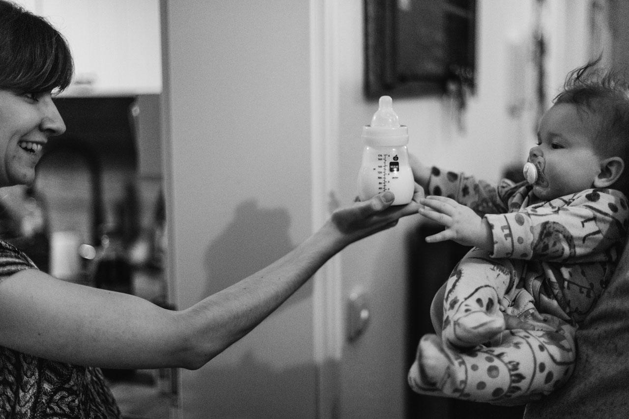 Mutter reicht dem Baby die Trinkflasche