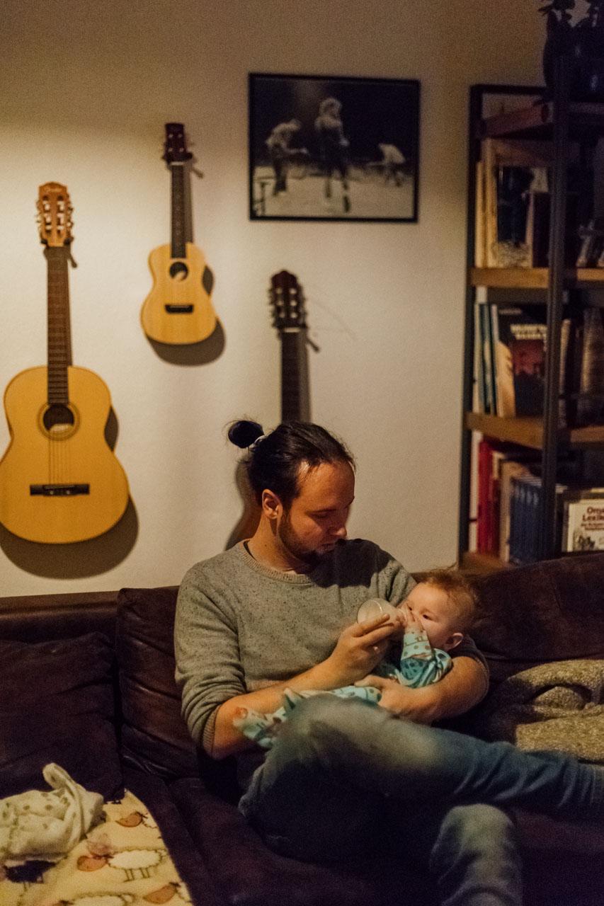 Vater sitzt auf der Couch und gibt den Kind Milch.