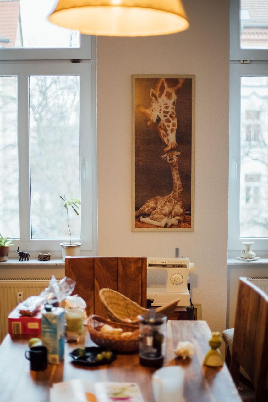ein gedeckter Frühstückstisch, darüber leuchtet eine Lampe
