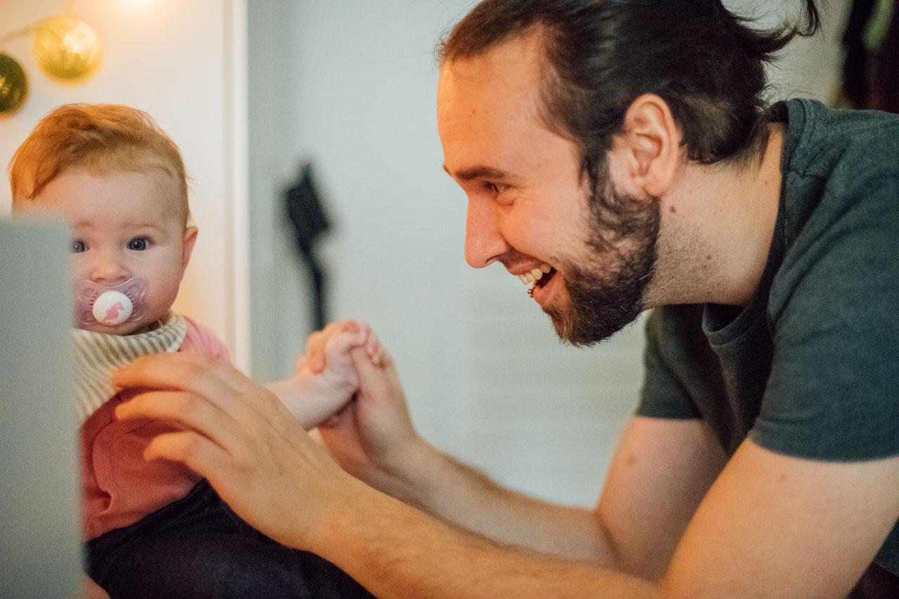Vater kitzelt das Baby und lacht dabei