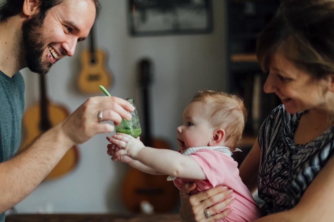 Baby sitzt auf den Schoß der Mutter und greift nach dem Glas mit Brei, welches der Vater hält
