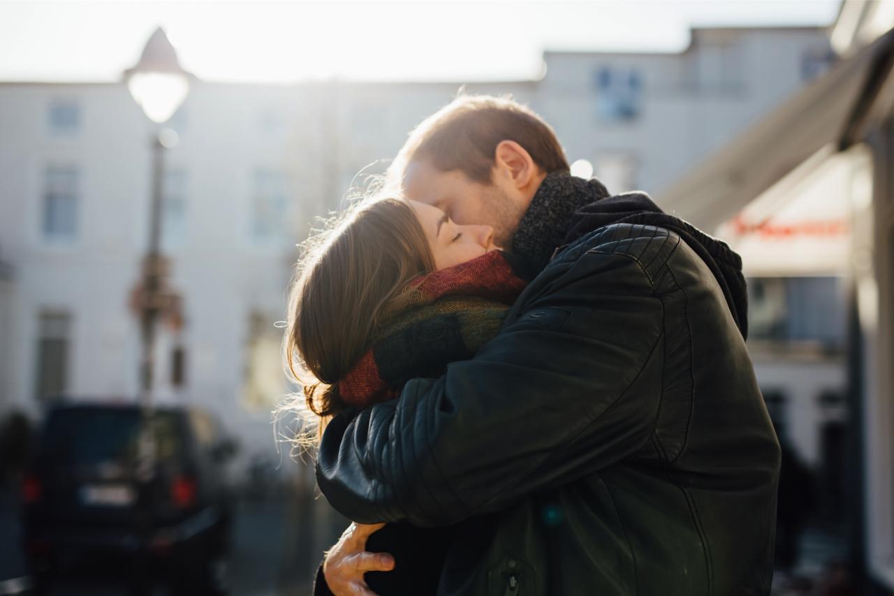 Paar liegt sich eng umschlungen in den Armen, vom Gegenlicht beleuchtet